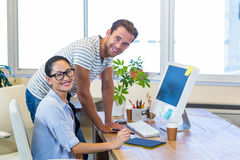 Smiling partners working together on computer Royalty Free Stock Photography