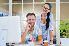Smiling partners working together on computer Royalty Free Stock Image