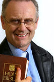 Smiling Pastor. Man dressed as a Pastor in a leather coat holding his bible Royalty Free Stock Photo