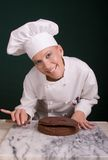 Smiling Pastry Chef. Close up capture of a smiling female Pastry Chef leveling a layer of chocolate devil's food cake using a large cake spatula Stock Images