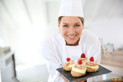 Smiling pastry chef with deserts. Smiling pastry chef showing desserts on plate Royalty Free Stock Photo