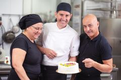 Smiling pastry Chefs showing a cake stock photos