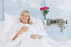 Smiling patient looking at camera on her bed Stock Image