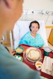 Smiling Patient Looking At Nurse Serving Breakfast. Mature smiling patient looking at nurse serving breakfast in hospital Stock Photography