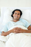 Smiling patient lying on a hospital bed Royalty Free Stock Image