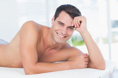 Smiling patient lying on massage table and looking at camera Royalty Free Stock Images