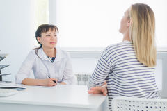 Smiling patient receiving a medical consultation and looking at camera, the female doctor is sitting at desk on the. Background Royalty Free Stock Photos