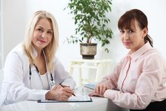 Smiling patient receiving a medical consultation and looking at camera, the female doctor is sitting at desk. Selective focus Stock Photography