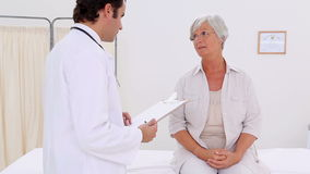 Smiling patient talking with her serious doctor Stock Photography