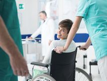 Smiling patient on wheelchair at the hospital. Smiling female disabled patient at the hospital meeting her doctor for a visit, a nurse is pushing her wheelchair Royalty Free Stock Images