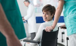 Smiling patient on wheelchair at the hospital. Smiling female disabled patient at the hospital meeting her doctor for a visit, a nurse is pushing her wheelchair Royalty Free Stock Photos