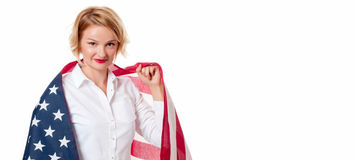 Smiling patriotic woman holding United States flag. USA celebrate 4th July. Royalty Free Stock Image