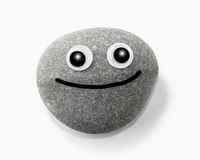 Smiling pebble. A close up of a round stone with big eyes and a happy smile Royalty Free Stock Image