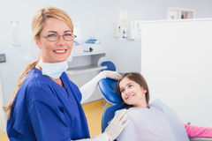 Smiling pediatric dentist with a happy young patient Royalty Free Stock Image