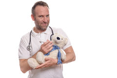 Smiling pediatric nurse with a teddy bear Royalty Free Stock Photos