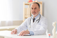 Smiling pediatrician sitting at table Royalty Free Stock Photo