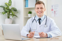 Smiling pediatrician sitting at the table Stock Photos