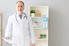 Smiling pediatrician standing at his office. What excellent physician. Handsome middle aged pediatrician in white coat standing with documentation and smiling Stock Image