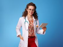 Smiling pediatrist woman using tablet PC on blue. Smiling pediatrist woman in white medical robe using tablet PC isolated on blue background Royalty Free Stock Images