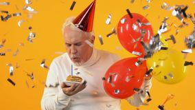 Smiling pensioner blowing cake candle falling confetti, birthday celebration. Stock footage stock video footage