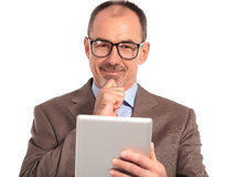 Smiling pensive mature businessman reading on tablet Royalty Free Stock Image