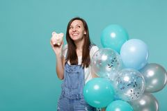 Smiling pensive woman in denim clothes looking up holding piggy money bank celebrating with colorful air balloons