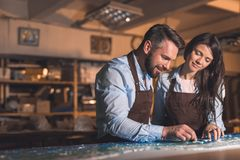Smiling people in aprons at work. In studio stock image