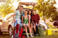 Smiling people on camping trip in the trunk make selfie. Happy smiling people on camping trip in the trunk make selfie while unpacking royalty free stock image