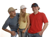 Smiling people in caps. Smiling 2 men in black cap and in beige cap and a woman in white cap and yellow T-short Royalty Free Stock Photography