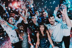 Smiling People Celebrating New Year on Party. Happy New Year. People Have Fun. Indoor Party. Celebrating of New Year. Young Woman in Dress. Young Man in Suit royalty free stock photography