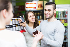 Smiling people choosing tinned food Royalty Free Stock Photo