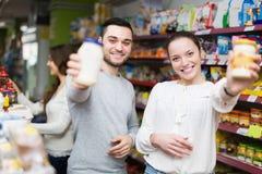 Smiling people choosing tinned food Royalty Free Stock Image