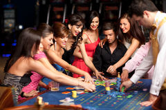 Smiling people and dealer playing roulette stock image