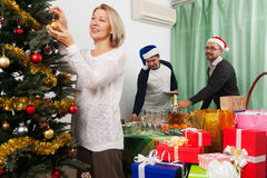Smiling people decorate Christmas tree Royalty Free Stock Photos