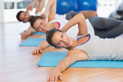 Smiling people doing pilate exercises in fitness studio Royalty Free Stock Photos
