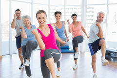 Smiling people doing power fitness exercise at yoga class. Portrait of smiling people doing power fitness exercise at yoga class in fitness studio royalty free stock image