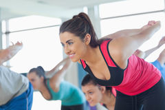 Smiling people doing power fitness exercise at yoga class Stock Photo