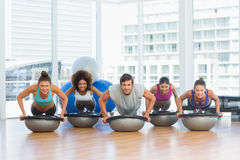Smiling people doing push ups in fitness studio Royalty Free Stock Images