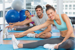 Smiling people doing stretching exercises Stock Image