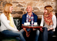Smiling people drinking coffee and having fun. Three friends in cafe discussing and having fun Stock Image