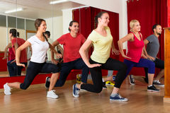 Smiling people exercising choreography. Happy smiling people wearing fitness clothes exercising choreography in gym stock photography
