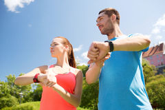 Smiling people with heart rate watches outdoors Stock Images