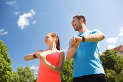 Smiling people with heart rate watches outdoors Royalty Free Stock Photos