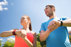 Smiling people with heart rate watches outdoors Stock Photos