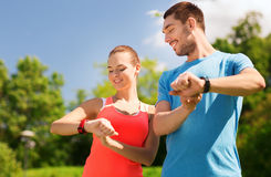 Smiling people with heart rate watches outdoors Royalty Free Stock Photography
