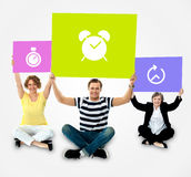Smiling people holding board in clock symbol stock photos