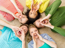 Smiling people lying down on floor and screaming. Education and happiness concept - group of young smiling people lying down on floor in circle screaming and Royalty Free Stock Photos