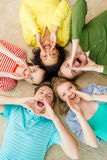 Smiling people lying down on floor and screaming. Education and happiness concept - group of young smiling people lying down on floor in circle screaming and Royalty Free Stock Photography