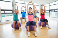 Smiling people sitting on exercise balls and stretching up hands Stock Photos