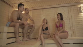 Smiling people are soaring in the hot sauna. Four friends are talking with each other. The camera moves from men to girls. Two attractive men and two young stock footage